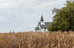 Beautiful little country church sitting behind a golden barley field. stock photography