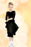 Beautiful little dancer in a black dress. The slender little blonde girl dancer in the long dress of black color made specifically for performing .The girl royalty free stock photo