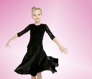 Beautiful little dancer in a black dress. The slender little blonde girl dancer in the long dress of black color made specifically for performing .The girl stock photo