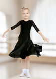 Beautiful little dancer in a black dress. The slender little blonde girl dancer in the long dress of black color made specifically for performing .The girl stock images