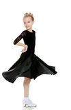 Beautiful little dancer in a black dress. The slender little blonde girl dancer in the long dress of black color made specifically for performing . The girl royalty free stock image