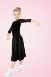Beautiful little dancer in a black dress. The slender little blonde girl dancer in the long dress of black color made specifically for performing .The girl held stock images