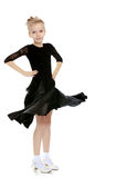 Beautiful little dancer in a black dress. The slender little blonde girl dancer in the long dress of black color made specifically for performing .Girl spinning royalty free stock photos