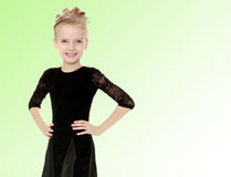 Beautiful little dancer in a black dress. The slender little blonde girl dancer in the long dress of black color made specifically for performing .A girl stands royalty free stock photo