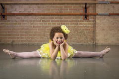 Beautiful little dancer portrait at a dance studio. Cute African American little dancer stretching her legs as she gets ready to dance at her dance studio stock photo
