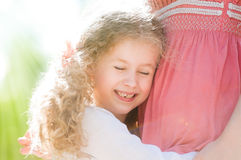 Beautiful little daugher hugging her mother Stock Photos