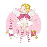 Сute Christmas fairy. Beautiful little fairy. She`s blonde. Princess dancing in a ballerina costume. She is wearing socks with a Christmas pattern  and a red Stock Image