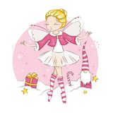 Сute Christmas fairy. Beautiful little fairy. She`s blonde. Princess dancing in a ballerina costume. She is wearing socks with a Christmas pattern  and a red Royalty Free Stock Images