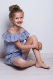 Beautiful little fashion model on white background. Portrait of cute smiling girl posing in studio. Stock Photos