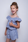 Beautiful little fashion model on white background. Portrait of cute smiling girl posing in studio. Stock Images