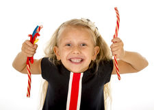 Beautiful little female child with blue eyes eating strawberry licorice candy Royalty Free Stock Photography