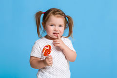 Beautiful little female child holding huge lollipop spiral candy smiling happy  on blue background. Stock Image
