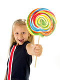 Beautiful little female child with sweet blue eyes holding huge lollipop spiral candy smiling happy. Beautiful little female child with sweet blue eyes and long Royalty Free Stock Photo