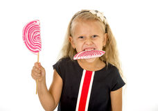 Beautiful little female child with sweet blue eyes and long blond hair eating huge lollipop spiral candy Royalty Free Stock Images