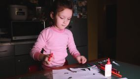 Beautiful little female preschool European child in pink sweater sitting by the table at home cutting paper shapes. stock video