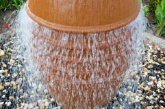 A beautiful little fountain in the form of a brown vase, a jug with falling drops of water on colored stones standing stock photo