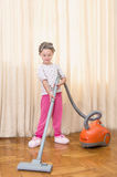 Beautiful little gir. L helping mother to clean the room - sitting on the vacuum cleaner Royalty Free Stock Image