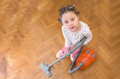 Beautiful little gir. A Vacuuming girl looking up Royalty Free Stock Images