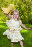 Beautiful little girl. Beautiful little girl jumping and have fun holding a straw hat in summer royalty free stock image