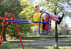 Beautiful little girl. On swing in childrens city park Royalty Free Stock Photos