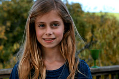 Beautiful Little Girl. A beautiful little girl with a blue shirt and a green leafy background Royalty Free Stock Photos