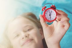 Beautiful little girl with alarm clock on bed in the bedroom. stock images