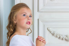 A beautiful little girl angel in white robe praying Stock Photo