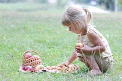 Beautiful little girl with apples on the nature Stock Photos