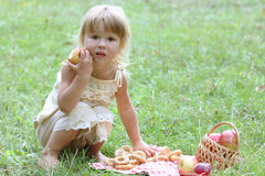 Beautiful little girl with apples on the nature Stock Image