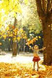 Beautiful little girl in the autumn park playing in nature Stock Photography