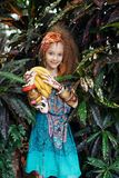 A beautiful little girl with bananas wearing native costume in the jungle or rainforest. Stock Photography