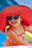 The beautiful little girl in a bathing suit. And a hat swims in the pool Stock Photos