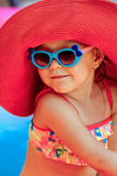 The beautiful little girl in a bathing suit. And a hat swims in the pool Stock Photography