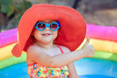 The beautiful little girl in a bathing suit and a hat swims in t. He pool Stock Images