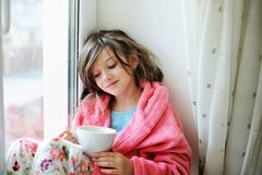 Beautiful little girl in bathrobe with cup of tea Stock Photo