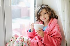 Beautiful little girl in bathrobe with cup of tea Stock Image