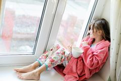 Beautiful little girl in bathrobe with cup of tea Royalty Free Stock Photos
