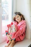 Beautiful little girl in bathrobe near window Royalty Free Stock Photos