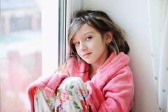 Beautiful little girl in bathrobe near window Royalty Free Stock Photos