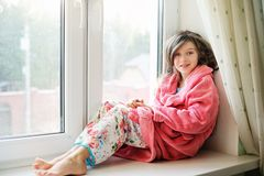 Beautiful little girl in bathrobe near window Stock Images