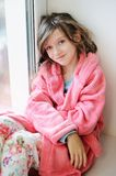 Beautiful little girl in bathrobe near window Stock Image