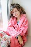 Beautiful little girl in bathrobe near window Stock Image
