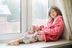 Beautiful little girl in bathrobe near window Royalty Free Stock Image