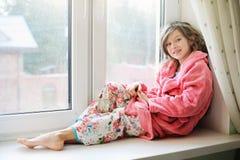 Beautiful little girl in bathrobe near window Royalty Free Stock Image