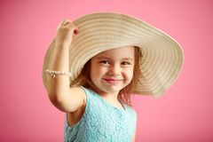 Beautiful little girl in beach hat stands over pink isolated background. royalty free stock photography