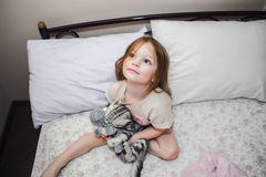 Beautiful little girl in bed with her ​​pet Royalty Free Stock Photography