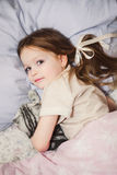 Beautiful little girl in bed with her pet Royalty Free Stock Photo