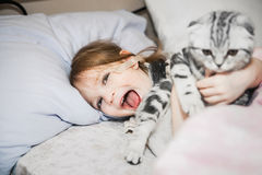 Beautiful little girl in bed with her ​​pet Stock Photos