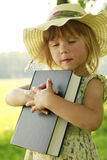 Beautiful little girl with the Bible in nature Royalty Free Stock Images