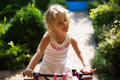 Beautiful little girl on a bicycle in the park, summer outdoor Royalty Free Stock Photo